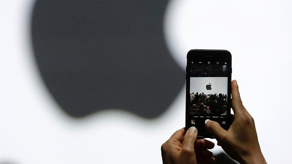 FILE - In this Monday, June 5, 2017, file photo, a person takes a photo of an Apple logo before an announcement of new products at the Apple Worldwide Developers Conference in San Jose, Calif. Apple is expected to demand $  1,000 for the fanciest iPhone that it has ever made, thrusting the market into a new financial frontier that will test how much consumers are willing to pay for a device that has become an indispensable part of modern life. (AP Photo/Marcio Jose Sanchez, File)