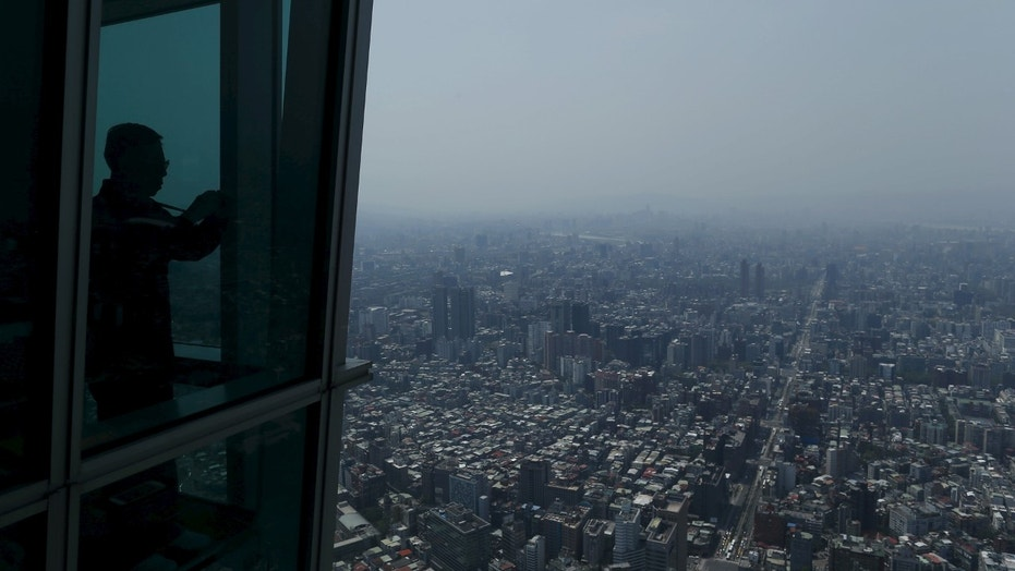 File photo - A tourist takes a photo of the city skyline from the Taipei 101 skyscraper building in Taipei, Taiwan March 29, 2016. (REUTERS/Tyrone Siu)