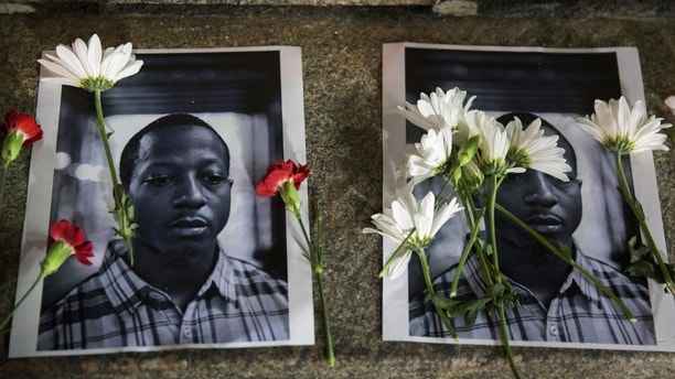 Flowers rest on top of pictures of Kalief Browder in New York June 11, 2015. New York City Mayor Bill de Blasio on Monday vowed to push reforms at the city's troubled Rikers Island prison complex after the reported weekend suicide of the 22-year-old Browder who had been held there for three years without being convicted of a crime. REUTERS/Lucas Jackson  - GF10000124813