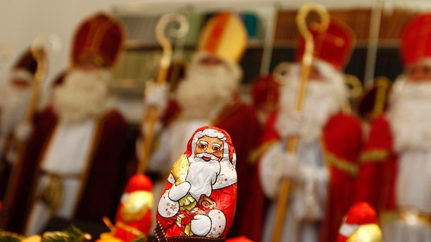 Tax and legal professionals dressed in St. Nicholas costumes are pictured behind a chocolate Santa Claus, during a meeting to receive instructions for their participation in St. Nicholas Day festivities, in Munich November 8, 2012. Each year a group of volunteers made up of tax consultants, lawyers, a school director and an orthodontist, dress-up as St. Nicholas to distribute sweets and small presents to children to celebrate St. Nicholas Day. Over two-days the 24 St. Nicholas' will visit 70 families, social projects and orphanages in Munich with private donations. St. Nicholas Day is traditionally celebrated on December 6.  Picture taken November 8.  REUTERS/Michaela Rehle (GERMANY - Tags: RELIGION SOCIETY) - BM2E8B81N9I01