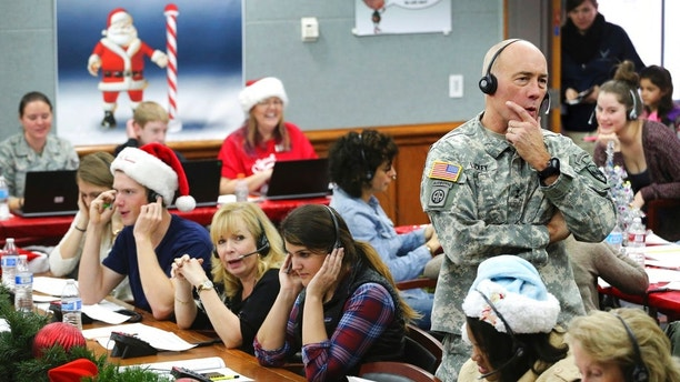 FILE - In this Dec. 24, 2014, file photo, NORAD and USNORTHCOM Chief of Staff Maj. Gen. Charles D. Luckey joins other volunteers taking phone calls from children around the world asking where Santa is and when he will deliver presents to their homes, inside a phone-in center during the annual NORAD Tracks Santa Operation, at the North American Aerospace Defense Command, at Peterson Air Force Base, Colo. Hundreds of volunteers are on the phones at the base, answering questions from eager kids who want to know where Santa is on his Christmas Eve travels. (AP Photo/Brennan Linsley, File)
