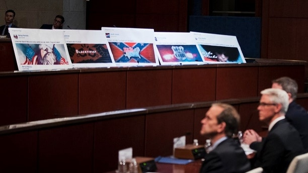 Facebook ads linked to a Russian effort to disrupt the American political process are displayed as, from left, Google's Senior Vice President and General Counsel Kent Walker, Facebook's General Counsel Colin Stretch, and Twitter's Acting General Counsel Sean Edgett, testify during a House Intelligence Committee hearing on Capitol Hill in Washington, Wednesday, Nov. 1, 2017. (AP Photo/Manuel Balce Ceneta)