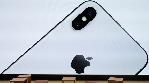 An iPhone X is seen on a large video screen in the new Apple Visitor Center in Cupertino, California, U.S., November 17, 2017. REUTERS/Elijah Nouvelage - RC14F23DD5E0
