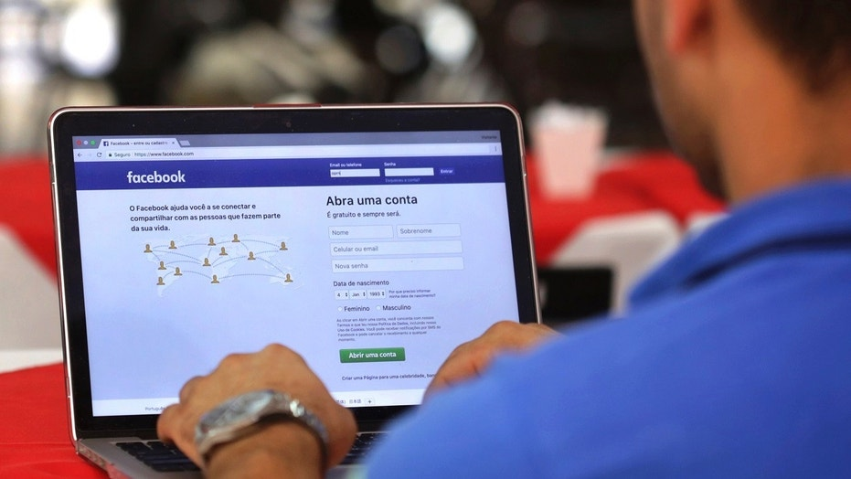 FILE - In this Thursday, Jan. 4, 2018, file photo, a man demonstrates how he enters his Facebook page as he works on his computer at a restaurant in Brasilia, Brazil. Facebook users will soon see more local news and more posts from friends and family as the company tries to give users more �meaningful social interactions,� as CEO Mark Zuckerberg said recently. (AP Photo/Eraldo Peres, File)