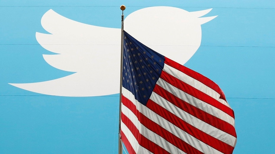 The Twitter Inc. logo is shown with the U.S. flag during the company's IPO on the floor of the New York Stock Exchange in New York, Nov. 7, 2013.