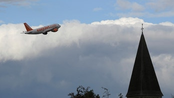 An EasyJet passenger aircraft is seen behind a church steeple as it takes off from Gatwick Airport in southern England, Britain, October 9, 2016. REUTERS/Toby Melville - S1BEUFZZIBAA