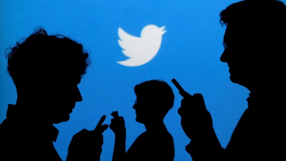 FILE PHOTO: People holding mobile phones are silhouetted against a backdrop projected with the Twitter logo in this illustration picture taken September 27, 2013. REUTERS/Kacper Pempel/Illustration/File Photo - S1AEUIPASIAA
