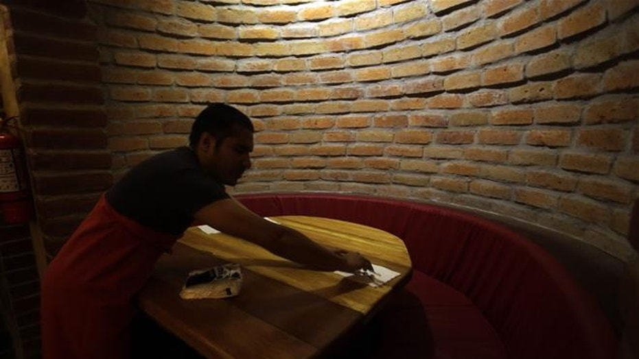 A waiter cleans an empty table at La Cueva de Rafa in Quito, Ecuador.