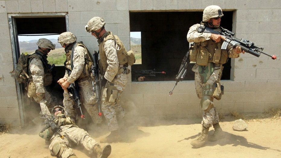 """File photo - U.S. Marines carry a """"wounded"""" soldier, injured by a simulated improvised explosion, during a simulated training of a search through an Iraqi city built at the U.S. Marine Base in Camp Pendleton, California, June 29, 2006. (REUTERS/Mike Blake)"""