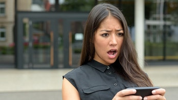 Young woman reacting in horror to an sms, text message or email on her mobile phone as she stands outdoors in a quiet urban street, close up head and shoulders