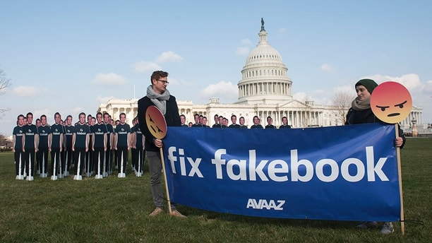Avaaz campaigners hold a banner in front of 100 cardboard cutouts of the Facebook founder and CEO stand outside the U.S. Capitol, before Mark Zuckerberg testifies before the Senate, in Washington on Tuesday, April 10, 2018. Advocacy group Avaaz is calling attention to hundreds of millions of fake accounts still spreading disinformation on Facebook, and calling for the social media giant to submit to an independent audit. (Kevin Wolf / AP images for AVAAZ)