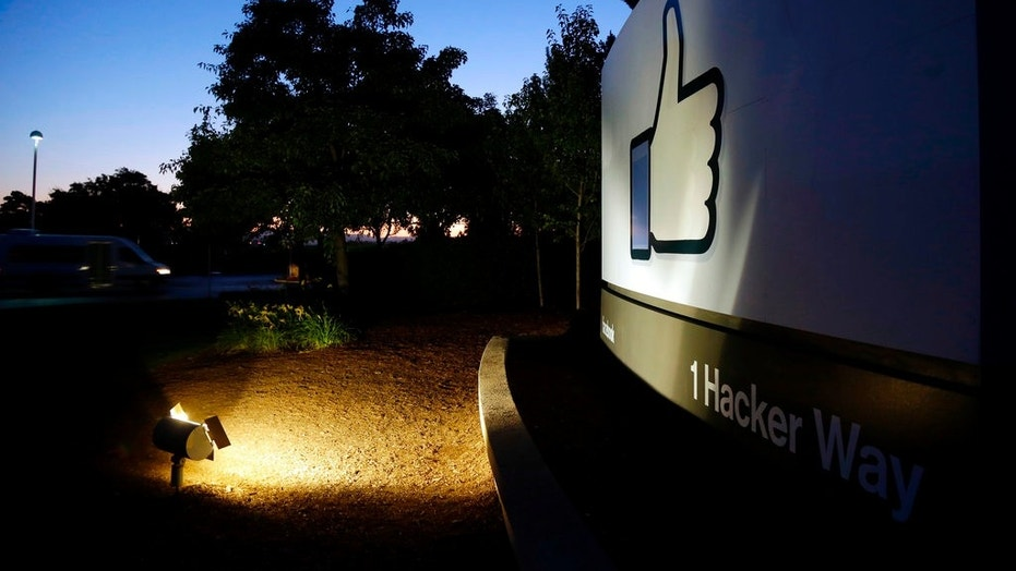 """FILE - In this Jun 7, 2013, file photo, the Facebook """"like"""" symbol is illuminated on a sign outside the company's headquarters in Menlo Park, Calif. (AP Photo/Marcio Jose Sanchez)"""