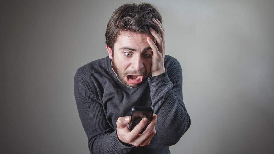 Shocked and frightened young caucasian man checking his phone, terrified with its content  (This content is subject to copyright.) (Credit: iStock)