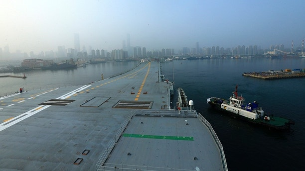 In this photo provided by China's Xinhua News Agency, China's aircraft carrier leaves Dalian in northeast China's Liaoning Province for sea trials Sunday, May 13, 2018.  China's first entirely home-built aircraft carrier has begun sea trials in a sign of the growing sophistication of the country's domestic arms industry.  State media said the still-unnamed ship left dock in the northern port of Dalian early Sunday, and the Liaoning provincial maritime safety bureau issued an order for shipping to avoid a section of ocean southeast of the city between Sunday and Friday. (Hu Kaibing/Xinhua via AP)