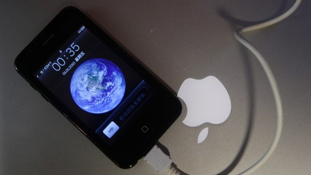 A posed picture shows a fake iPhone 3GS charging next to an Apple logo on a Macbook Air laptop in Beijing July 22, 2011. A fake Apple store in China, made famous by a blog that said even the staff working there didn't realise it was a bogus outlet, is probably the most audacious example to date of the risks Western companies face in the booming Chinese market. The less-publicised phenomenon of unauthorised vendors setting up shop to peddle real products has grown alongside China's manufacturing prowess. Many of the factories that produce brand-name goods on contract have been known to do extra runs of the goods to make extra cash, analysts say.     REUTERS/Jason Lee (CHINA - Tags: BUSINESS SOCIETY SCI TECH IMAGES OF THE DAY) - GM1E77M1QEP01