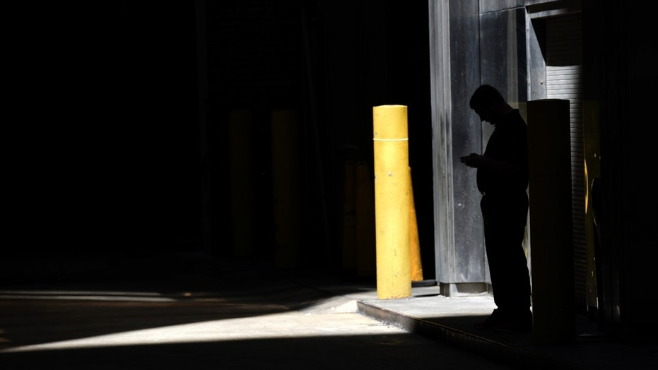 FILE- In this June 6, 2017, file photo, a man checks his phone in an alley in downtown Chicago. A security researcher says a website flaw at a U.S. company could have allowed anyone to pinpoint the location of nearly any cellphone in the United States. The lapse at LocationSmart, a company that gathers real-time data on cellular wireless devices, is the latest to highlight how little protection consumers have from trafficking in data about their location. (AP Photo/G-Jun Yam, File)