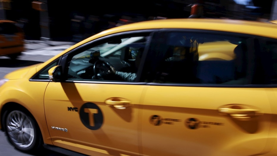 File photo - A New York City taxi cab drives through Times Square in New York March 29, 2016. (REUTERS/Lucas Jackson)