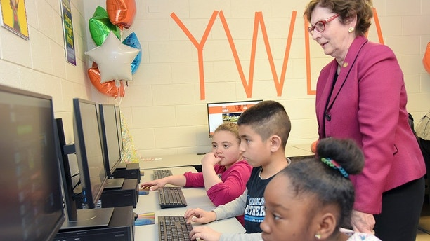 In a Friday, Jan. 26, 2018 photo, IGT, in partnership with the North Carolina Education Lottery, unveiles its latest After School Advantage technology lab at the YWCA of High Point. Sen. Trudy Wade watches as nine-year-olds Aaliya Coulson, left, Alexander Resendiz and Jalaia Pearce log on to computers in the new technology lab after a ribbon cutting and grand-opening ceremony. (Laura Greene/The High Point Enterprise via AP)