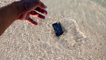 The Mobile phone fall to the sea water on the beach.