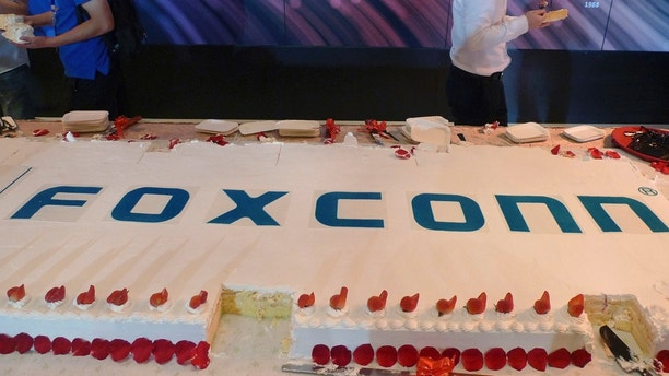 Workers walk past a giant cake to celebrate Taiwan-based contract manufacturing giant Foxconn's 30th anniversary of its first investment in Shenzhen, south China's Guangdong province Wednesday, June 6, 2018. The head of Taiwan's Foxconn, which assembles Apple iPhones and other tech products, says Washington's dispute with China is over technology rather than trade. (AP Photo/Kelvin Chan)