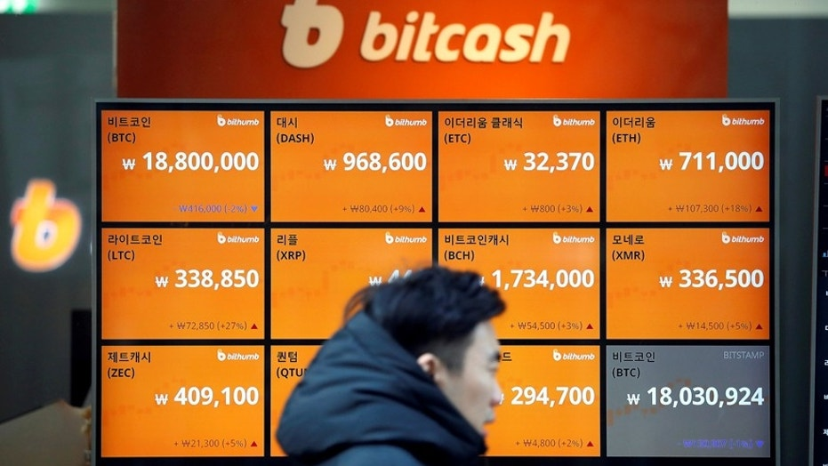 A man walks past an electric board showing exchange rates of various cryptocurrencies including Bitcoin (top L) at a cryptocurrencies exchange in Seoul, South Korea December 13, 2017.  REUTERS/Kim Hong-Ji - RC161BA31E70