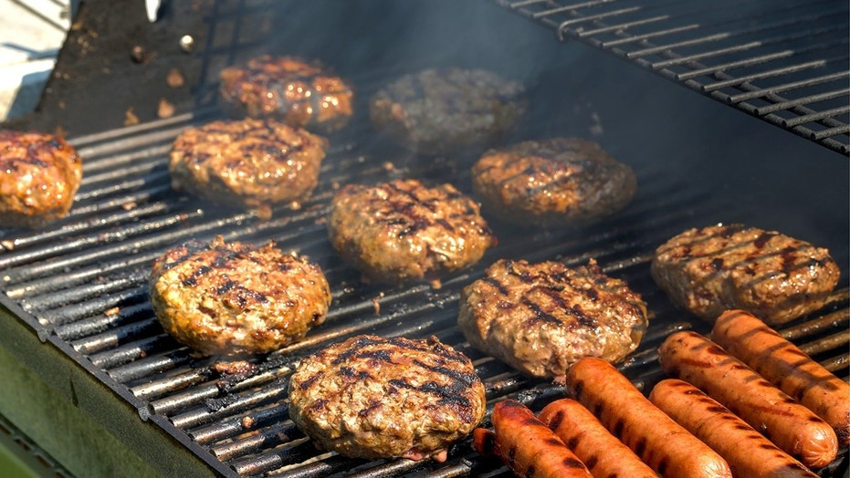 Cheeseburgers, hamburgers and hotdogs being grilled (Credit: iStock)