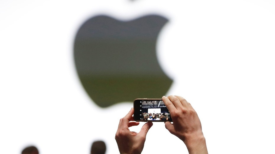 An audience member takes a photo of the Apple logo before the start of the company's annual developer conference in San Jose, California, U.S. June 5, 2017. REUTERS/Stephen Lam - RTX3959D
