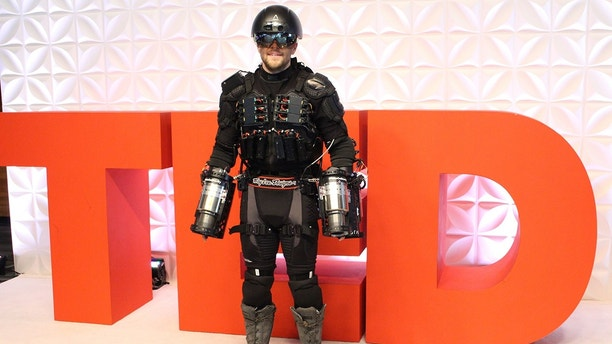 """Gravity founder Richard Browning fields questions about his personal flight suit at a TED Conference in Vancouver, Canada, on April 27, 2017.Using thrusters attached to his arms and back, Browning flew in a circle and hovered a short distance from the ground, captivating attendees of a prestigious TED Conference with the demonstration. The personal flight suit is capable of propelling wearers much higher and faster, according to its creators. / AFP PHOTO / Glenn CHAPMAN / TO GO WITH AFP STORY BY Glenn CHAPMAN """"US-Canada-Britain-lifestyle-aviation-technology-TED-Gravity""""""""        (Photo credit should read GLENN CHAPMAN/AFP/Getty Images)"""