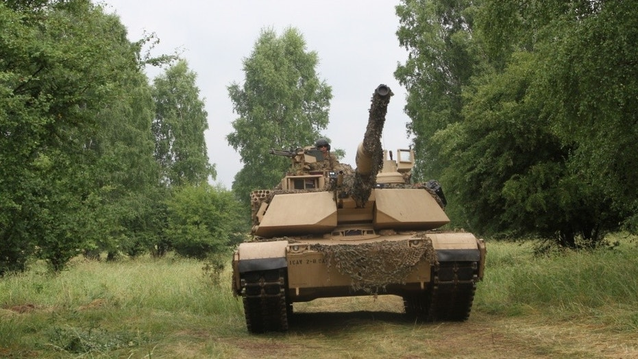 """File photo - Tank crewmen from Bravo Company """"Eager Arms"""", 2nd Battalion, 8th Regiment, 1st Armored Brigade Combat Team, 1st Cavalry Division maneuver a M1A2 Abrams tank during their company-level situational training exercise in preparation for Saber Strike in Drawsko Pomorskie Training Area, Poland, on June 12, 2018. (U.S. Army National Guard photo by Staff Sgt. Ron Lee, 382nd Public Affairs Detachment, 1ABCT, 1CD/Released)"""