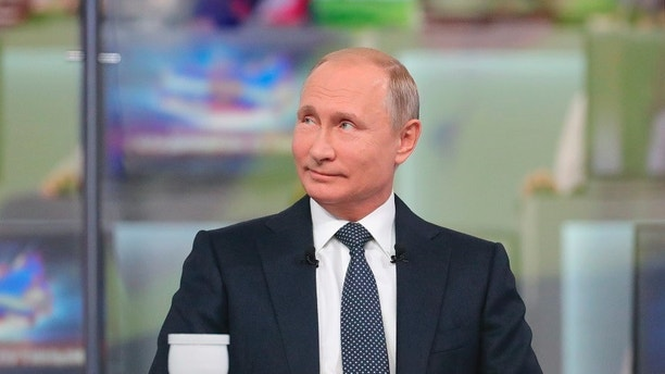 """Russian President Vladimir Putin smiles while answering a question during his annual call-in show in Moscow, Russia, Thursday, June 7, 2018. Speaking at the opening of his annual call-in television show, Putin said on Thursday that Russia's gross domestic product is currently 1.5 percent higher than a year ago. He described it as modest but said he is confident that future """"growth is guaranteed."""" (Mikhail Klimentyev, Sputnik, Kremlin Pool Photo via AP)"""