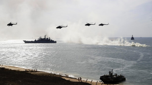 Russian navy ships and helicopters take a part in a landing operation during military drills at the Black Sea coast, Crimea, Friday, Sept. 9, 2016. Russia has deployed cruise missiles, multiple rocket launchers, tanks and its latest anti-aircraft system at massive military drills in Crimea. The drills which began across southern Russia and Crimea earlier this week and involve over 120,000 troops are some of the largest exercises Russia has held for years. (AP Photo/Pavel Golovkin)
