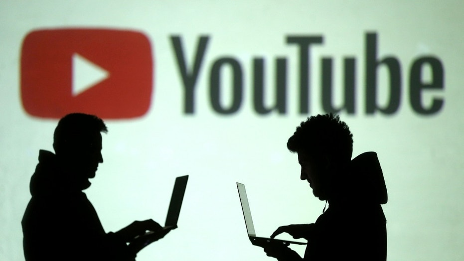 Silhouettes of mobile device users are seen next to a screen projection of Youtube logo in this picture illustration taken March 28, 2018.  REUTERS/Dado Ruvic/Illustration - RC1502FFC0B0