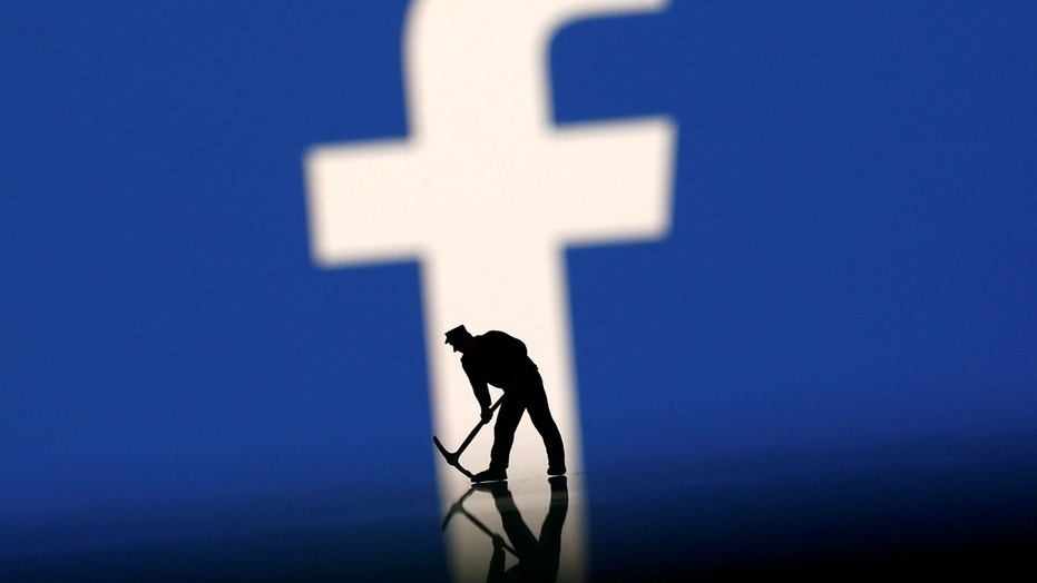 A figurine is seen in front of the Facebook logo in this illustration taken