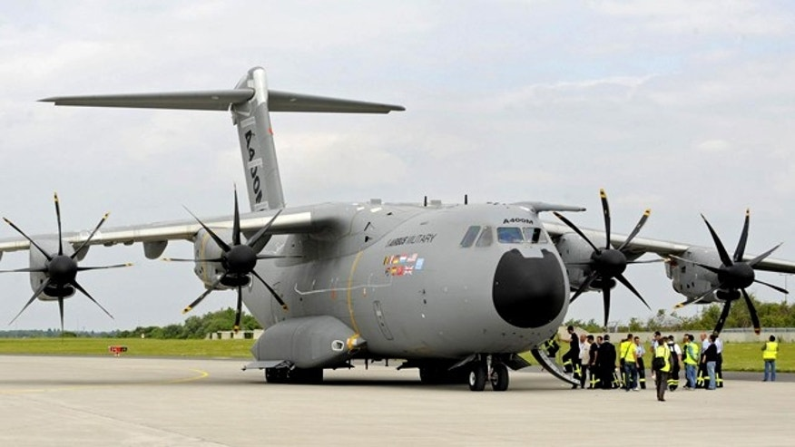 The military transport aircraft of Airbus A400M stands at the airfield prior to the start of  the International Air Show ILA at Schoenefeld airport in Berlin on Monday, June 7, 2010. A400M makes  its first public appearance at the Air Show. Visitors will be able to get an exclusive first glimpse of the aircraft, the all-new airlifter for the 21st Century and Airbus Military's latest development. The ILA 2010 will take place in Berlin between June 8 and June 13, 2010. (AP Photo/Jens Meyer)