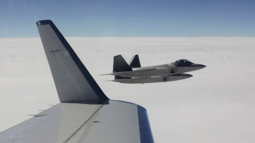 Two U.S.-built NORAD F-22 fighter jets fly alongside a civilian airplane playing the role of a hijacked airliner, Sunday, Aug. 8, 2010 on a route from Alaska to an undisclosed location in the Far East. The exercise is a first-of-its-kind joint exercise between the U.S. and Russia to test their coordinated response to a potential international hijacking. Later in the flight, Russian fighter jets also intercepted the flight as it passed through Russian airspace. (AP Photo/Ted S. Warren)