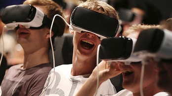 Persons with virtual reality headsets have fun at the gamescom fair in Cologne, Germany, Wednesday Aug. 23, 2017. The leading European trade fair for digital gaming culture is the meeting point for global companies from the entertainment industry and the international gaming community. (Oliver Berg/dpa via AP)