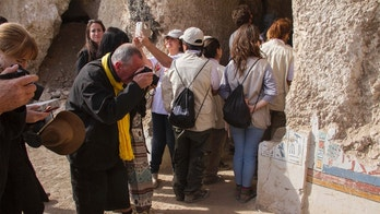 "Tourists photograph an entrance of a newly discovered tomb on Luxor's West Bank known as ""KAMPP 150"" during an announcement for the Egyptian Ministry of antiquities about new discoveries in Luxor, Egypt, Saturday, Dec. 9, 2017. Egypt's Antiquities Ministry says archaeologists have discovered two ancient tombs in the southern city of Luxor. The ministry said Saturday that one tomb has five entrances leading to a rectangular hall, and contains painted wooden funerary masks, clay vessels and a mummy wrapped in linen. (AP Photo/Hamada Elrasam)"