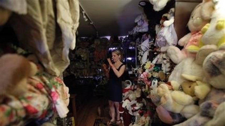 In this photo taken March 18, 2010, Erin Seeherman, of Philadelphia, takes pictures of stuffed bunnies while visiting the Bunny Museum in Pasadena, Calif. Guinness World Records dubbed The Bunny Museum the largest in 1999 when there were only 8,437 items in the house.(AP Photo/Jae C. Hong)