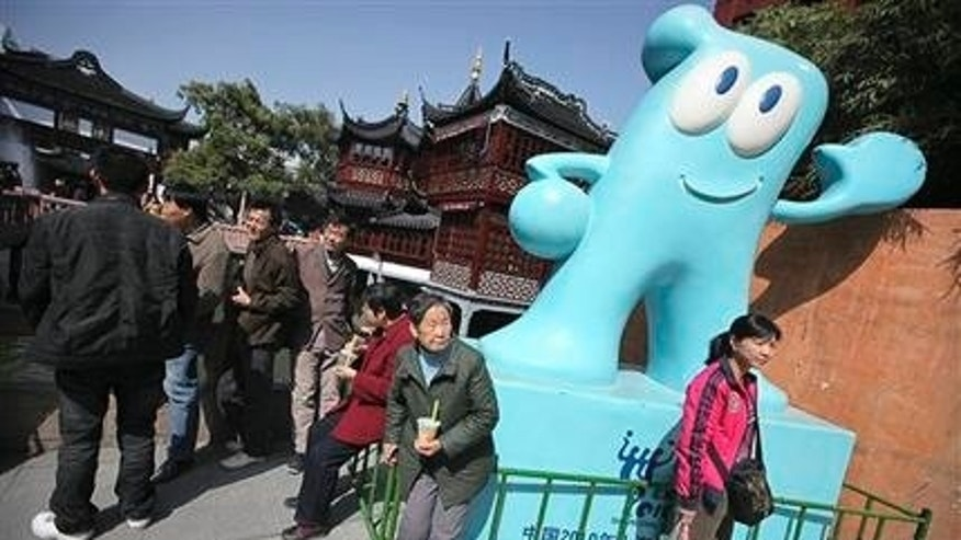 In this photo taken on March 17, 2010, tourists visiting Yu Garden huddle around a figure of Shanghai Expo's mascot Haibao in Shanghai, China. (AP Photo/Eugene Hoshiko)