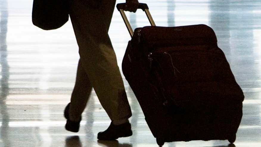 In this 2008 file photo, a person is seen rolling luggage at the Philadelphia International Airport. Spirit Airlines said Tuesday it will charge as much as $45 each way for a carry-on bag, adding a fee that bigger airlines have yet to try.
