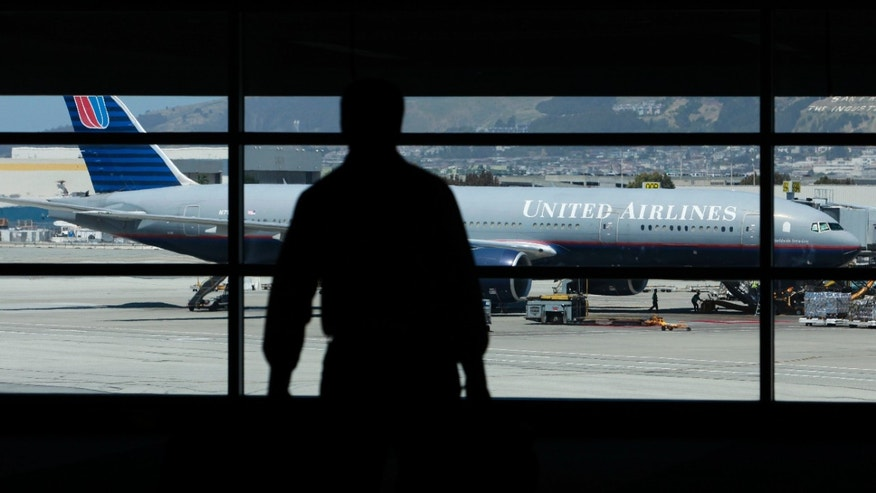 A United Airlines plane is shown as a man walks toward a terminal at San Francisco International Airport in San Francisco, Monday, May 3, 2010. United Airlines has agreed to buy Continental in a $3 billion-plus deal that would create the world's largest carrier with a commanding position in several top U.S. cities. (AP Photo/Jeff Chiu)