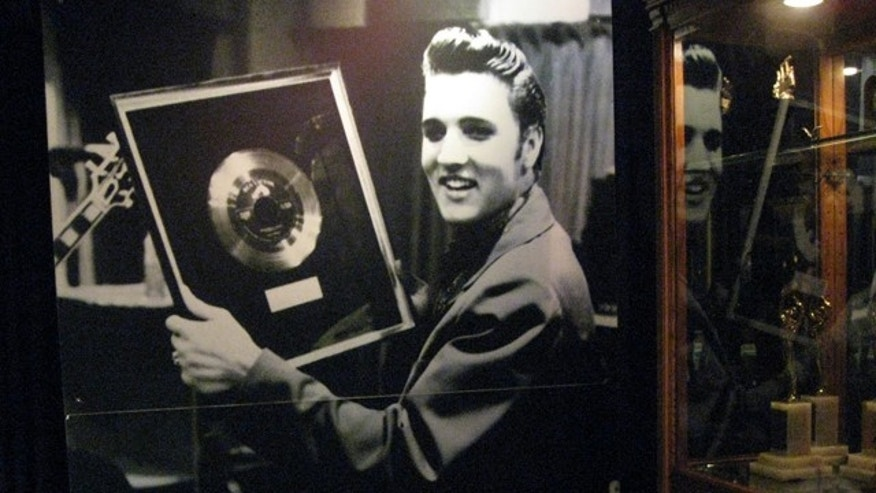 "Photo of Elvis holding the gold record for ""Heartbreak Hotel"" in the Trophy Building"