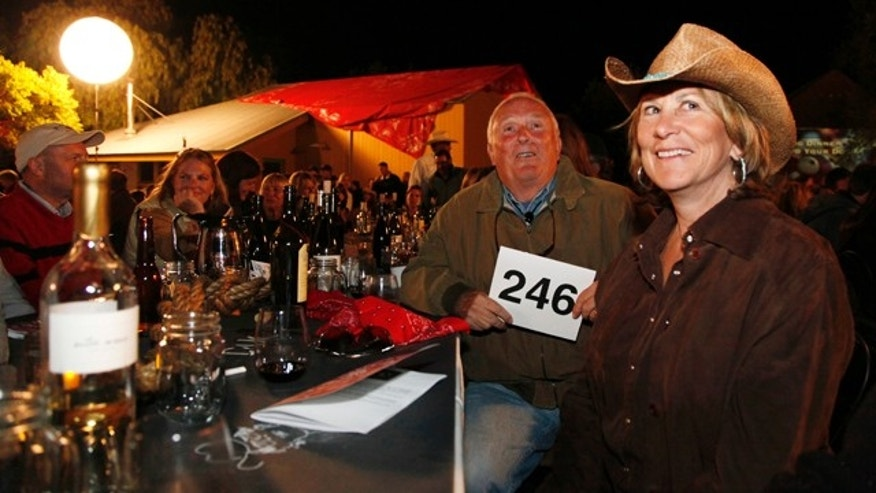 This Aug. 28, 2010 photo shows Dan Duckhorn, second from right, chairman and founder of the Duckhorn Wine Company and his wife Nancy Andrus Duckhorn, right, board member of  Napa Valley Grapegrowers, as they watch people bid during an auction at the grapegrowers STOMP harvest dinner at Hudson Vineyards in Napa, Calif. STOMP is an authentic food and wine celebration and gathering for Napa Valley wine enthusiasts to celebrate the imminent harvest season. (AP Photo/Eric Risberg)
