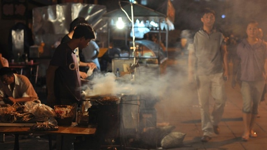 This August 2010 photo shows a food stand at a night market in Chifeng in China's Inner Mongolia. The night market in Chifeng offers a smorgasbord of knick-knacks and necessities, from beef kebabs and toys to underwear and sheets, stretching many blocks. In China's barely populated Inner Mongolian grasslands, what had defined Mongolian culture for outsiders have long been swapped for leather outfits, motorbikes, cell phones and tourism. (AP Photo/Sisi Tang)