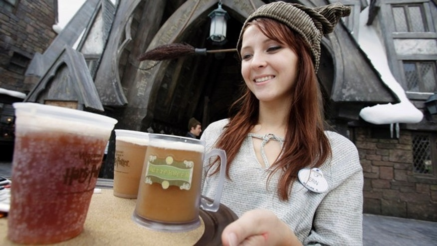This June 9, 2010 file photo shows Erin Wuchte as she serves up Butterbeer to guests at The Wizarding World of Harry Potter at Universal Orlando theme park in Orlando, Fla. Harry has conjured all the magic Universal expected, and then some. In the quarter after the attraction opened, crowds at Universal parks swelled by 36 percent over the same stretch last year, while attendance at Disney's Orlando parks stayed roughly the same.      (AP Photo/John Raoux, FILE)
