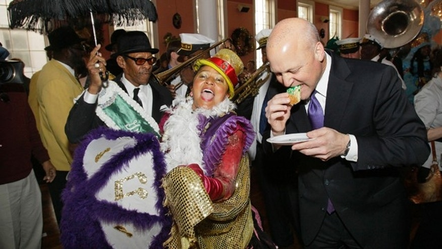 New Orleans Mayor Mitch Landrieu, right, takes a bite of traditional Mardi Gras king cake as a second line parade passes by during a ceremony to mark the beginning of carnival season in New Orleans, Thursday, Jan. 6, 2011. (AP Photo/Patrick Semansky)