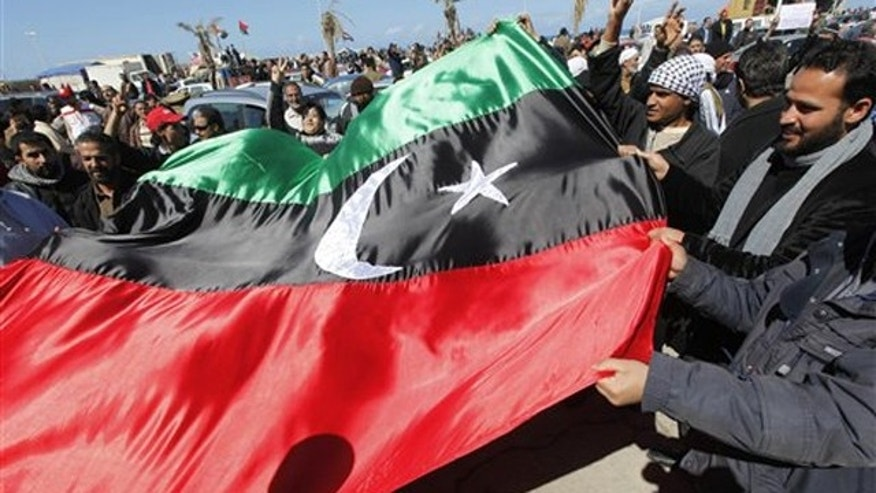 Libyan protesters wave the old Libyan flag in the Libyan city of Benghazi Feb. 28.