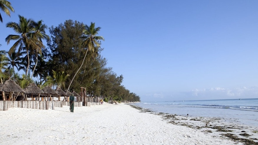 This Oct. 12, 2010 photo shows a villager walking along a deserted beach at Kiwengwa Strand Hotel Villagi Bravo, a seaside resort on the East African archipelago of Zanzibar. Kiwengwa Strand Hotel Villagi Bravo boasts brilliant white beaches and powdery soft sands fringed by tall coconut palms and lush vegetation.    (AP Photo/Rodrique Ngowi)