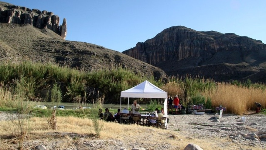 This March 26, 2011 photo shows campers as they assemble for dinner on the banks of the Rio Grande at Big Bend National Park, Texas. Far Flung Outdoor Center, a river outfitter from Terlingua, Texas, and San Antonio chef Francois Maeder conduct unique gourmet trips on the river offering white-linen table service in the wilderness,  hours from civilization.   (AP Photo/Michael Graczyk)