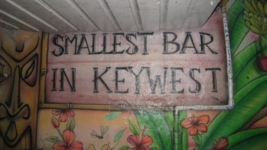 At Key West favorite 'Smallest Bar,' walls are painted with palm trees and waves, and there's a bin packed with hollowed-out coconuts and pineapples, which the bartender fills with beach-ready concoctions on demand.